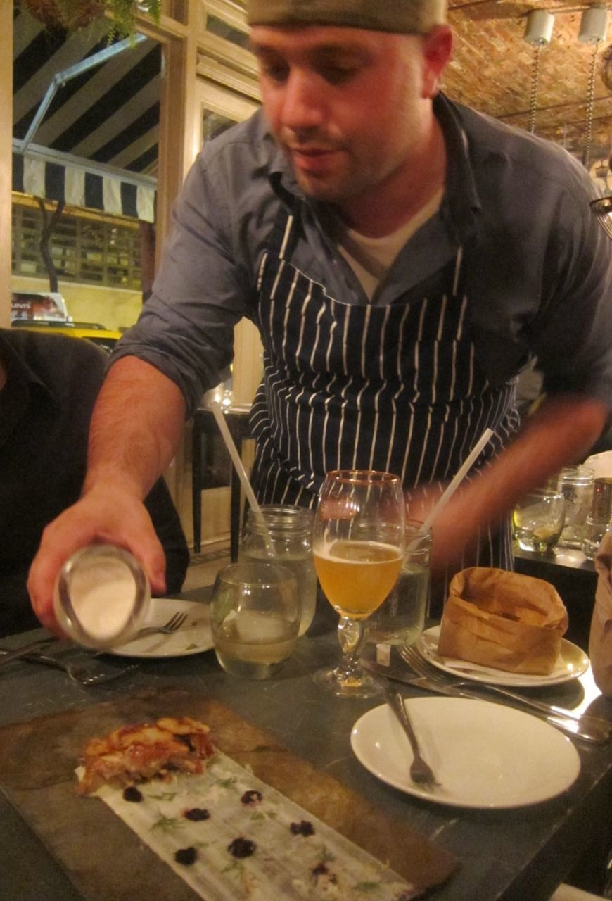 Chef Will Horowitz pours buttermilk dashi on smoked blue fish platter.