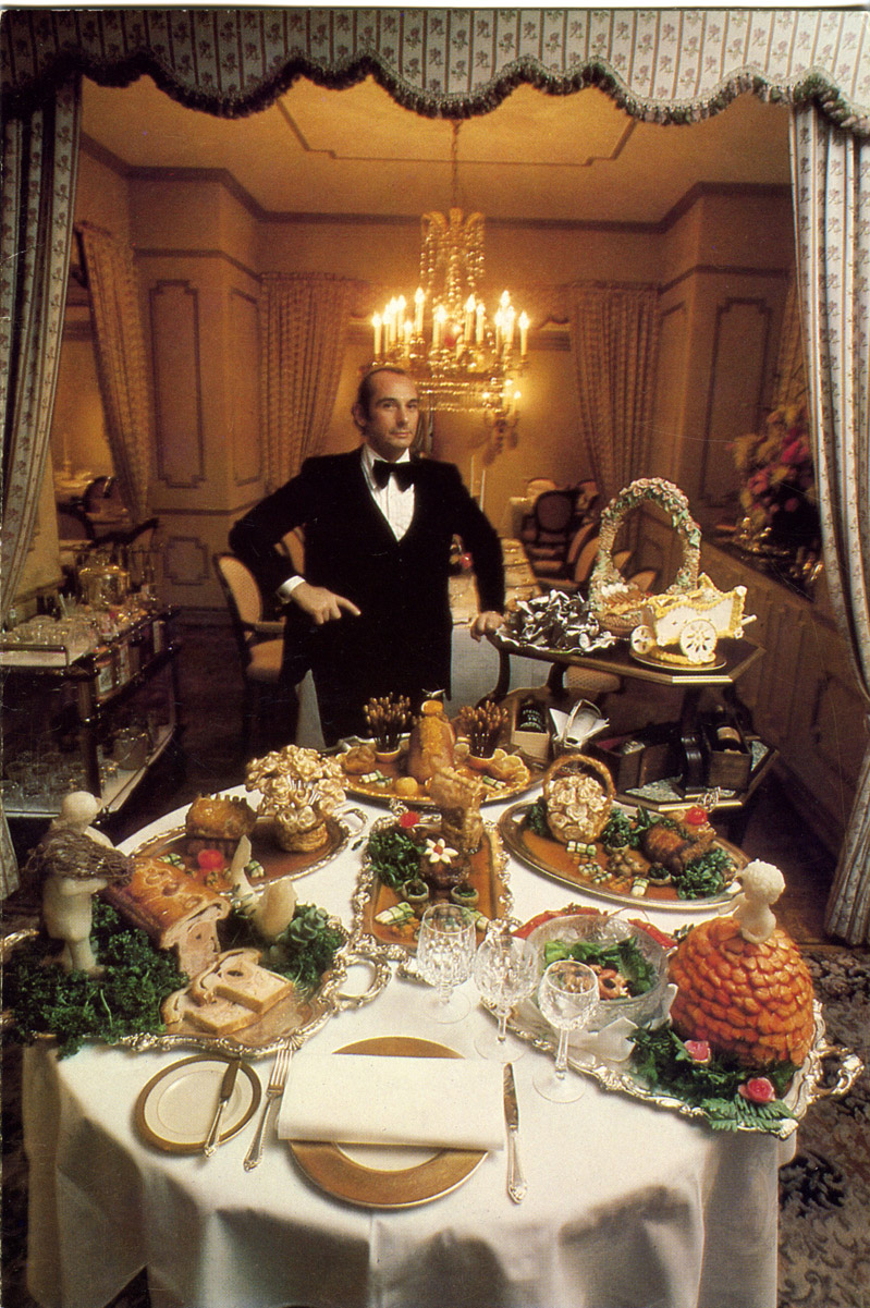 How dapper he is in velvet, Frank Valenza, Lord of the Palace surveys the chef's whimsies.