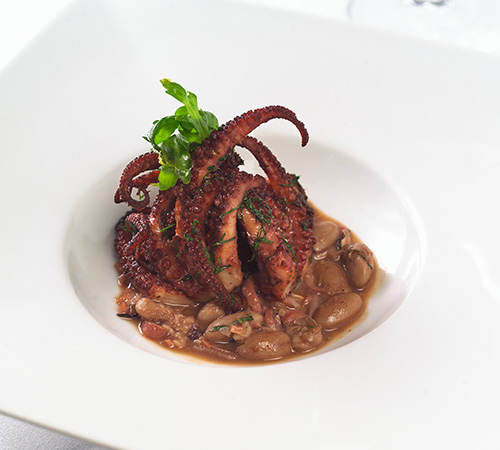 A pride of octopus wearing wild arugula rides on cranberry beans at Oceana.