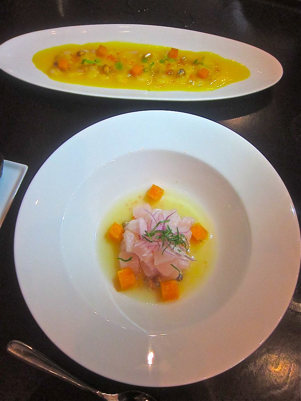 Corvina ceviche with sweet potato, top: wild bass tiradito in citrus tigre de leche