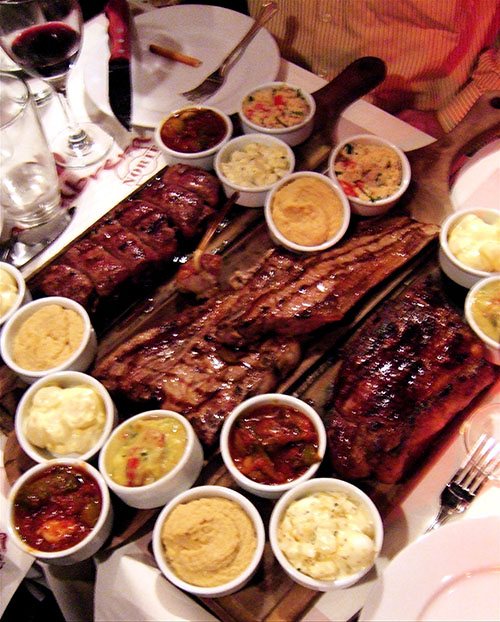 Slabs of meat with sauces and sides cover our table at Cabrera Norte. Photo:Steven Richter