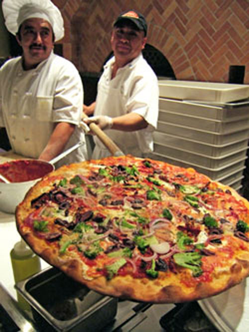 Pizzas at Dean's: The pizzaiolo shapes them. His elves bake them. Photo: Steven Richter